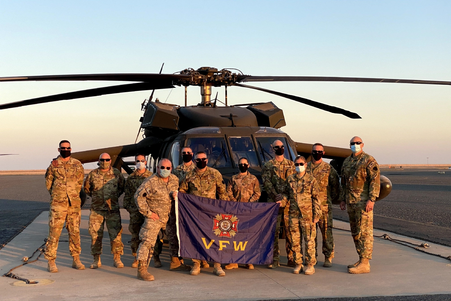 The 28th Infantry Division Expeditionary Combat Aviation Brigade poses with a VFW flag in front of a Blackhawk helicopter. The flag has traveled around the world to units with care packages. It hangs at PA VFW HQs with these photos around it. David Sandman, former Director of Communications, began the tradition.